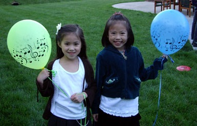 two young piano students holding musical looking balloons